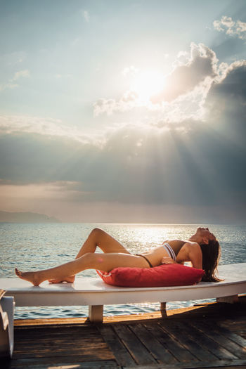 Water Sky Sunlight Real People Cloud - Sky Beauty In Nature Sun Lifestyles Sea Relaxation Nature One Person Leisure Activity Adult Women Young Women Young Adult Full Length Swimwear Lens Flare Horizon Over Water Outdoors Swimming Pool