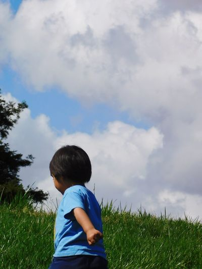 Rear view of boy walking on land against cloudy sky