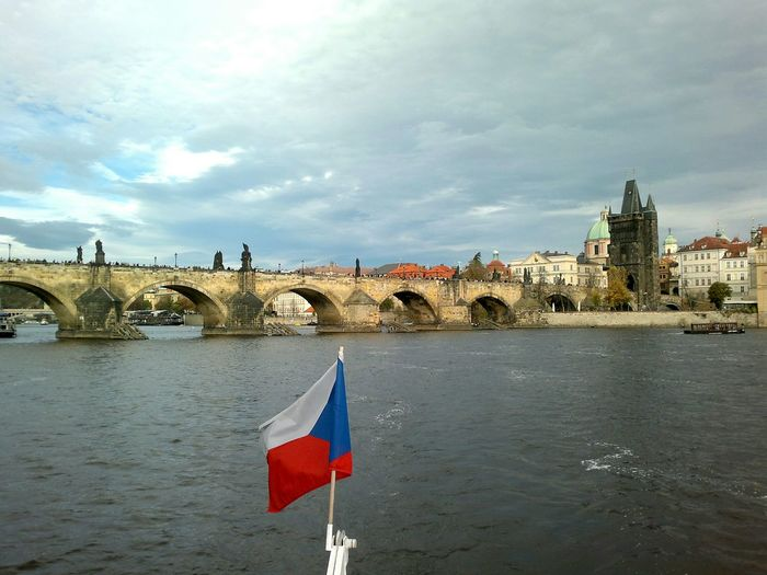 Czech flag by charles bridge against sky in city