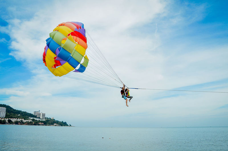 Low angle view of man paragliding over sea against sky