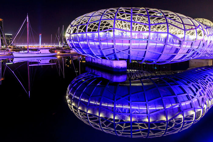 The Webb Bridge reflected in the Yarra River Amusement Park Architecture Blue Built Structure City Design Glowing Illuminated Light - Natural Phenomenon Lighting Equipment Nature Night Nightlife No People Outdoors Pattern Purple Reflection Shape Sphere Water