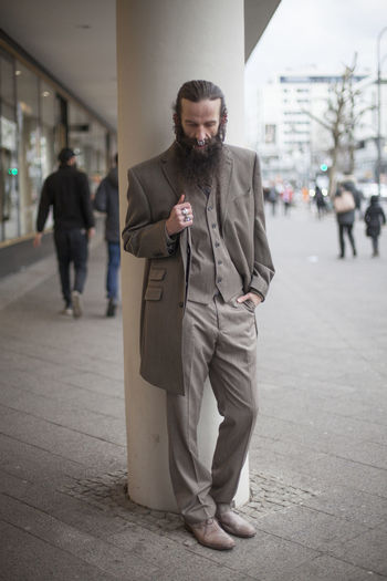 Thoughtful bearded mature man standing by column on footpath