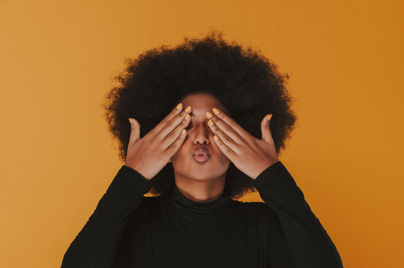 Beautiful young woman pouting while hands covering eyes against yellow background