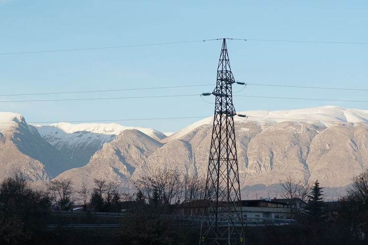 Electricity pylon on snow covered landscape against clear sky