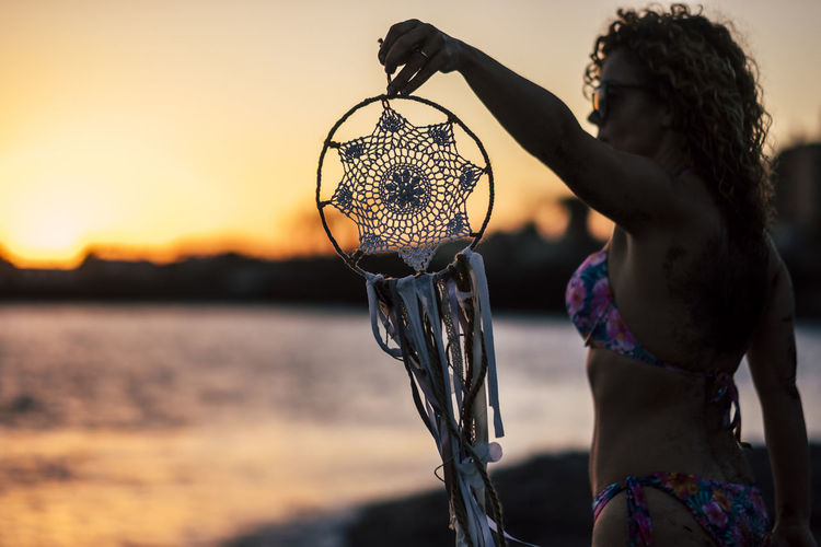 Woman Holding Dreamcatcher On Shore At Beach During Sunset