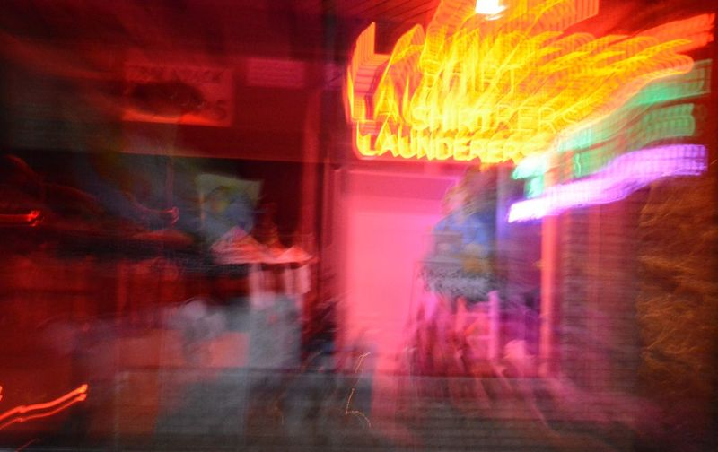 Defocused Image Of Illuminated Neon Sign On Window Display Of Shop