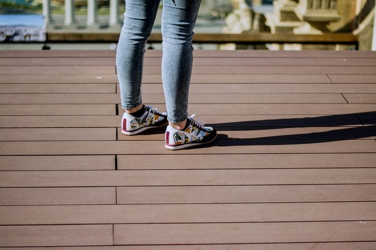 Low Section Of Woman Wearing Shoes Standing On Boardwalk During Sunny Day