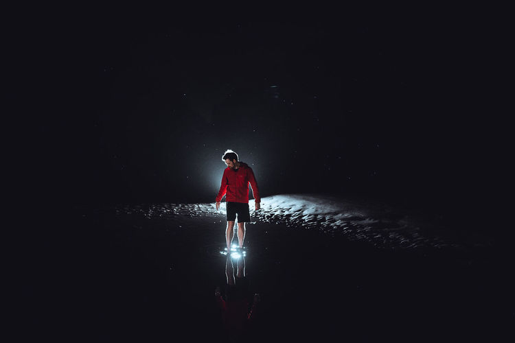 """And it's like walking in the space, every step you make, it's towards the unknown, the future. "" One Person Night Full Length Water Dark Nature Black Background Young Adult Illuminated Wet Standing Red Copy Space Adult Space Spotlight Solitude Outdoors Shorts Stars Fine Art Photography Conceptual Humanity Meets Technology"