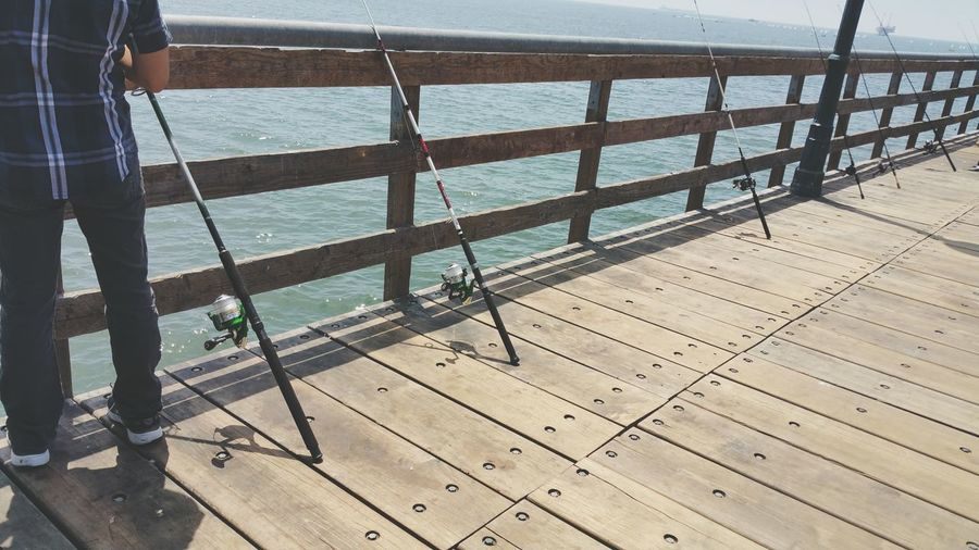 Low section of man standing on pier by fishing poles at railing against sea