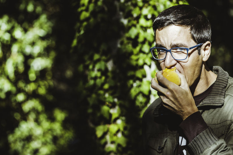 Young man with glasses and blue eyes biting a fruit, peach, with green leaves background Eyeglasses  Glasses One Person Holding Food And Drink Tree Food Freshness Fruit Real People Healthy Eating Plant Front View Leisure Activity Lifestyles Day Men Portrait Males  Outdoors Peach Biting Blue Eyes Eyesglasses Glasses