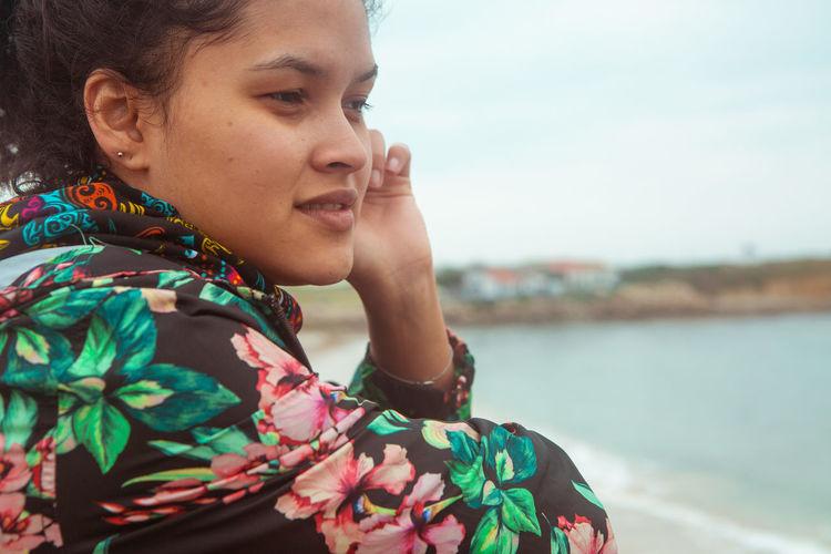 Woman looking away against lake