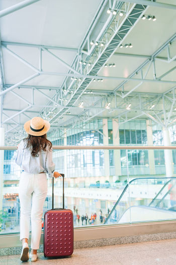 Rear view of woman with suitcase standing at airport