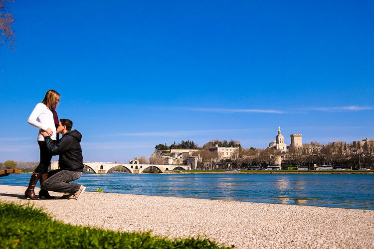 Couple At Riverbank Against Clear Blue Sky
