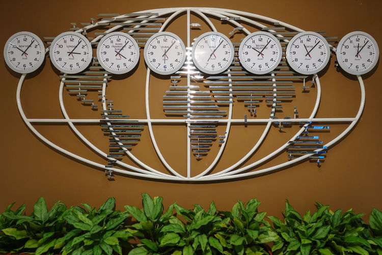 Close-up of clocks hanging against wall