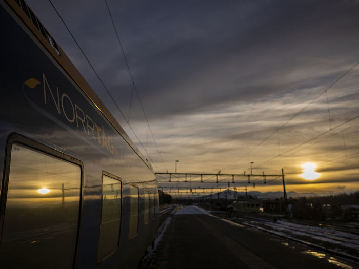 Reflection of sunrise Sky Sunset Cloud - Sky Transportation Nature Architecture Direction Connection No People The Way Forward Electricity  Cable Built Structure Illuminated Sun Lighting Equipment Outdoors Dusk Diminishing Perspective Light Norrtåg Train Reflection Railway Sunrise Capture Tomorrow