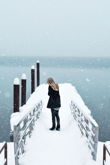 Woman standing on snow covered railing against clear sky