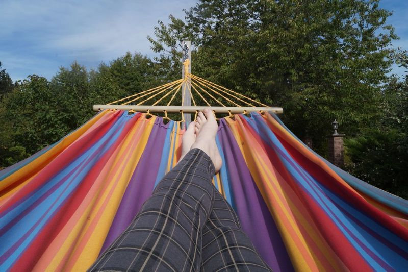 Low section of woman relaxing on hammock against trees