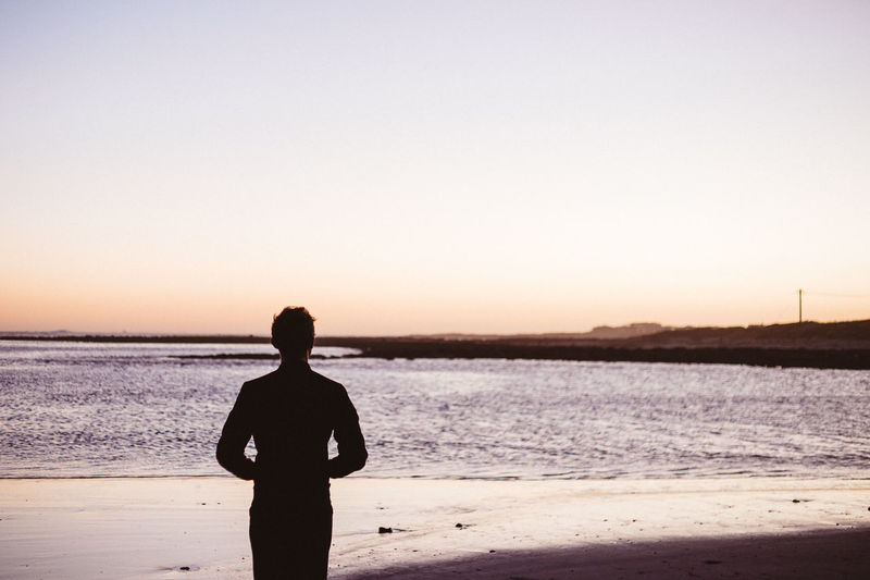 Silhouette man standing on beach against clear sky