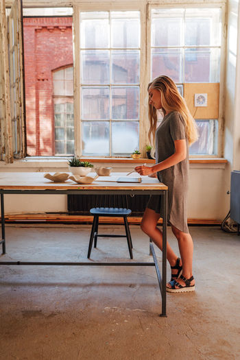 Side view of woman standing by table in workshop