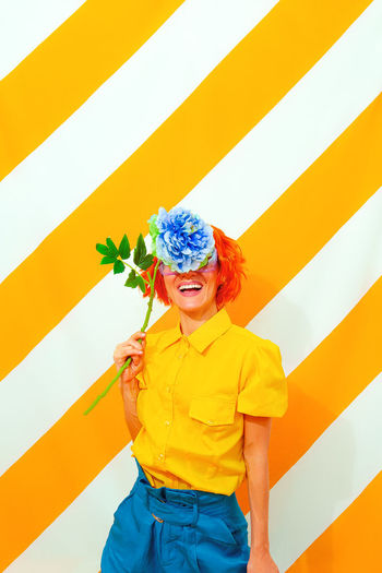 Smile woman on trend striped yellow background with flower in her hands. minimal