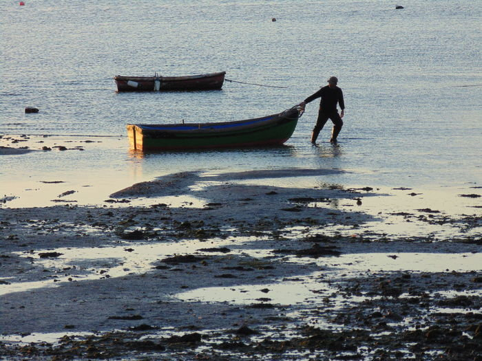 Man standing on boat moored at beach