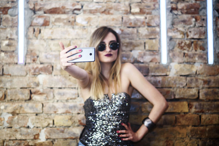 Fashionable young woman taking selfie against brick wall
