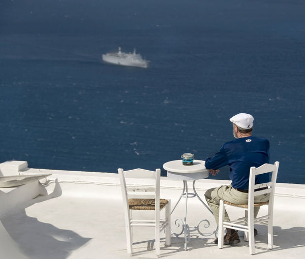 Casual Clothing Lifestyles Looking At View Man On Terrace Man On Terrace In Santor Man Watching Boat Pass Man Watching Cruise Sh Missed The Flight Outdoors Reflection Relaxation Sitting Vacations