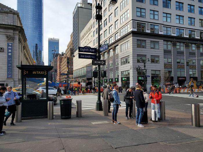 People walking on city street against buildings