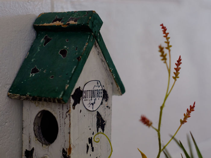 Low angle view of old birdhouse on wall