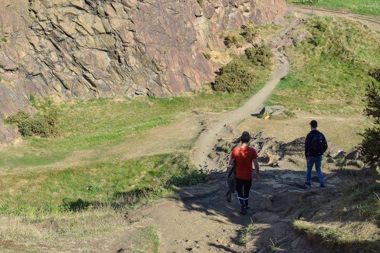 Rear view of men walking on mountain