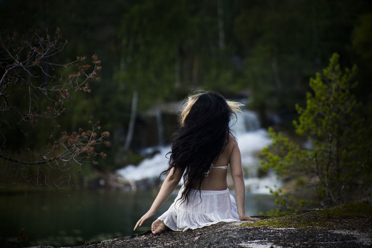 Rear view of woman sitting against waterfall in forest