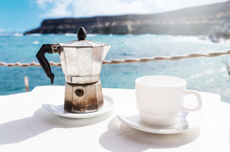 Close-Up Of Coffee On Table By Sea Against Sky