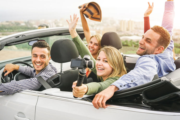 Friends driving on convertible car Car Convertible Cabrio Cabriolet People Holidays Vacation Mode Of Transportation Transportation Young Men Smiling Men Motor Vehicle Group Of People Happiness Young Adult Portrait Togetherness Land Vehicle Sitting Young Women Day Women Positive Emotion Arms Raised
