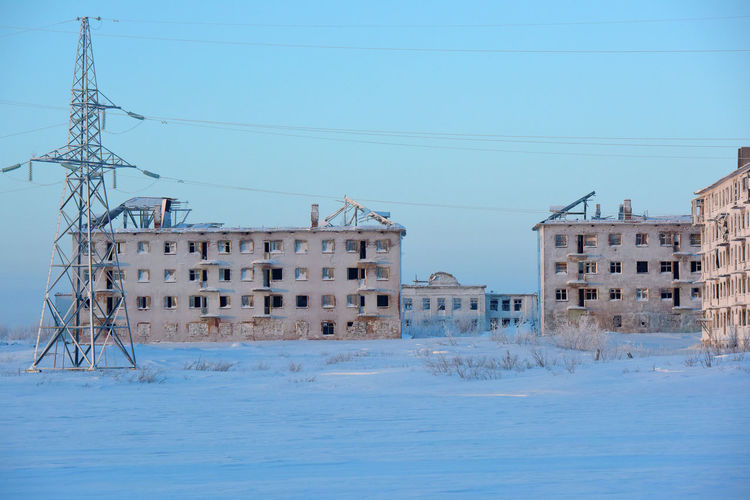 Buildings on snow covered landscape against clear blue sky