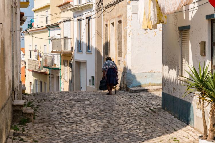 Rear view of woman walking along buildings