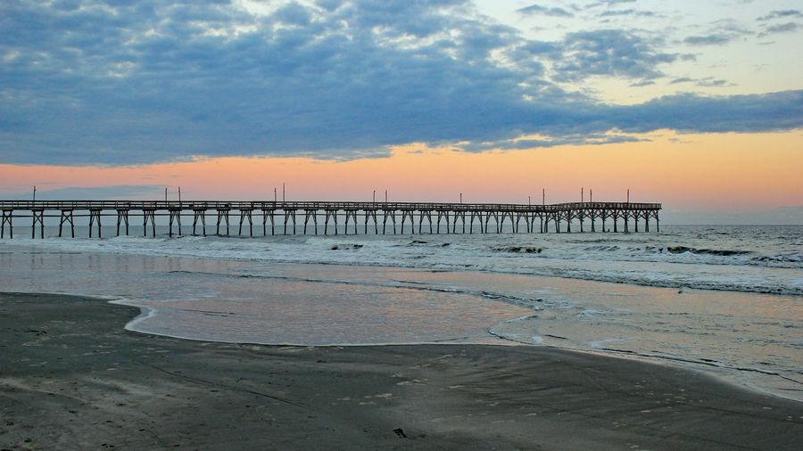 Pier On Beach Against Sky During Sunset