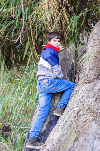 Portrait of teenage boy climbing on rock in forest
