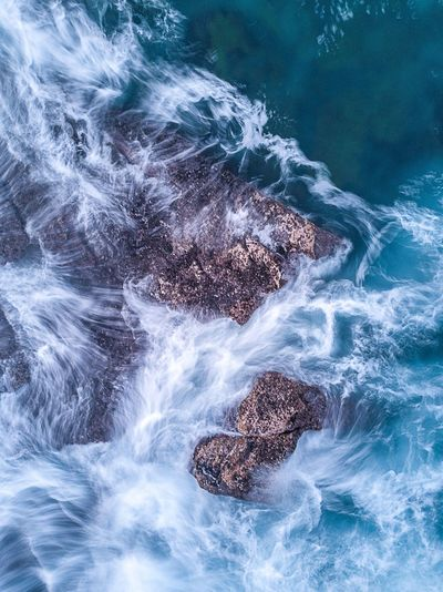 High angle view of sea splashing against rocks