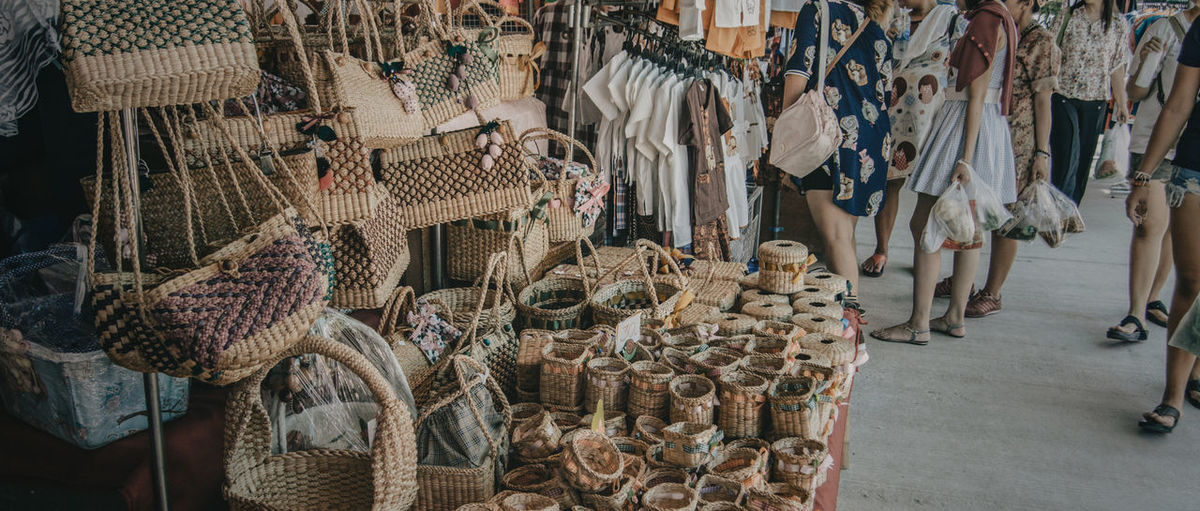 Low Section Of Women Standing By Woven Baskets And Handbags At Market