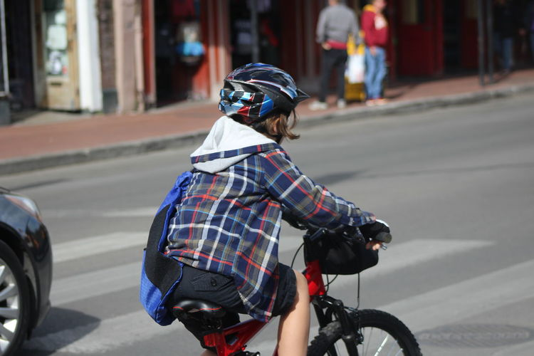 Baby Stroller Bicycle Cycling Day Focus On Foreground Full Length Headwear Helmet Incidental People Land Vehicle Leisure Activity Lifestyles Mode Of Transport Motorcycle One Person Outdoors Real People Rear View Riding Road Scooter Street Sunlight Transportation Walking