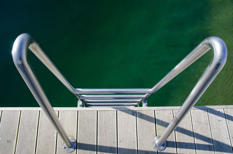 Directly above on a ladder going to the water. Beauty In Ordinary Things Business Day Design Directly Above Elevated View Geometric Shapes Ladder Light And Shadow Metal Metallic Minimalism Modern No People Outdoors Pier Protection Railing Safety Security Staircase Steps Steps And Staircases Water Wood - Material