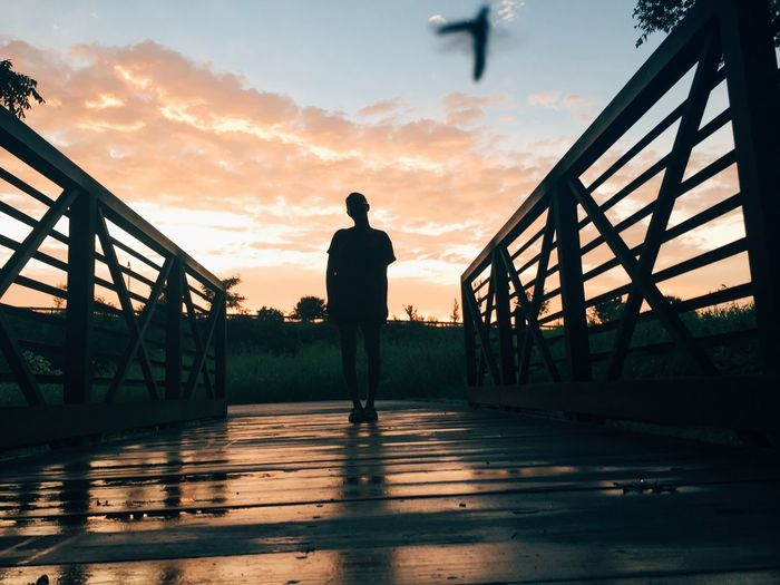 Silhouette man standing on footbridge against sky