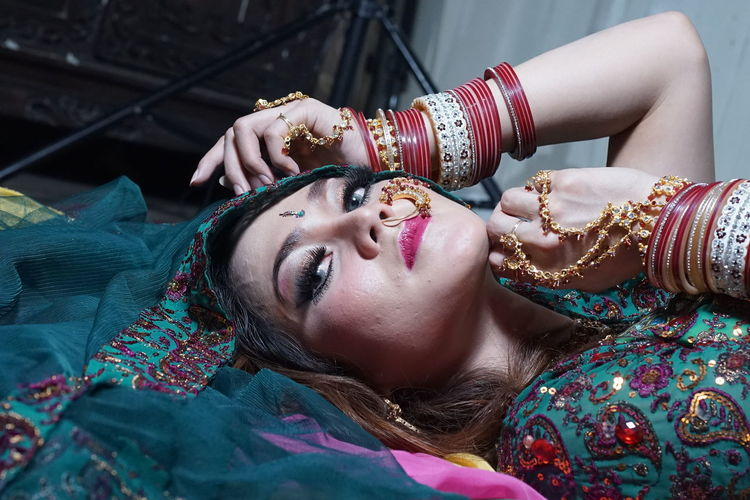 Portrait of beautiful woman wearing traditional clothing and jewelries while lying at home