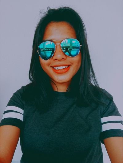 Portrait of smiling woman wearing sunglasses against white wall