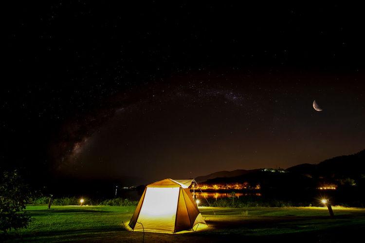 Illuminated lighting equipment on field against sky at night