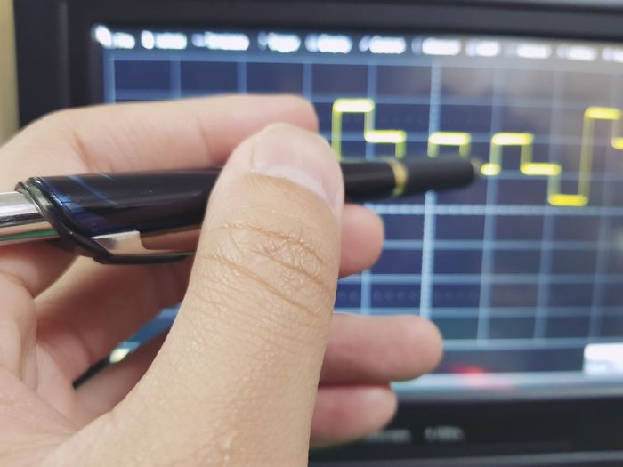 Close-up of person hand pointing on graph on device screen
