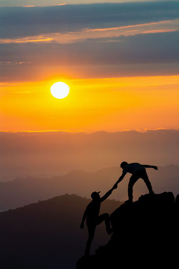 Sunset Silhouette Sky Orange Color Beauty In Nature Sun Scenics - Nature Real People Men Tranquil Scene Nature Climbing Tranquility Lifestyles Mountain Leisure Activity People Rock Cloud - Sky Two People Outdoors Trust Teamwork Help Together