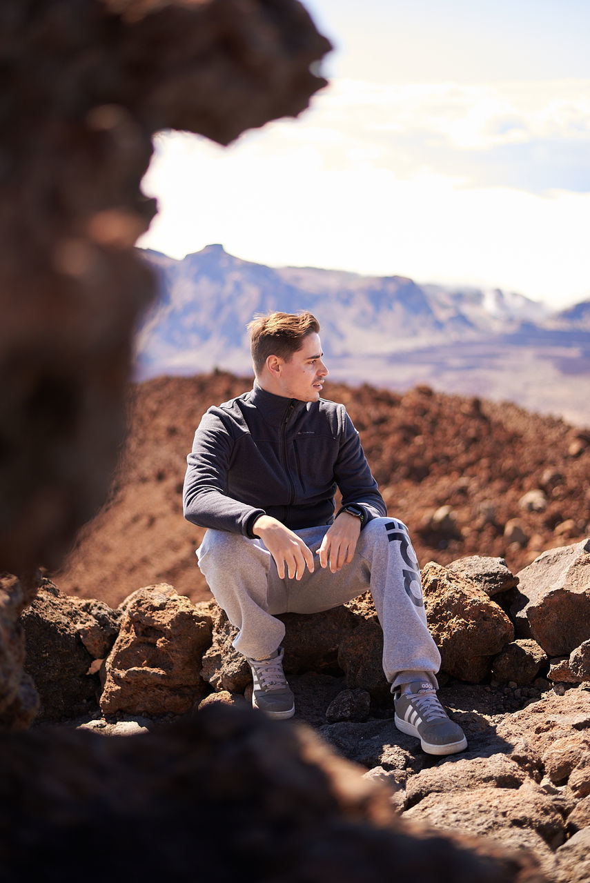 FULL LENGTH OF YOUNG MAN STANDING ON ROCKS
