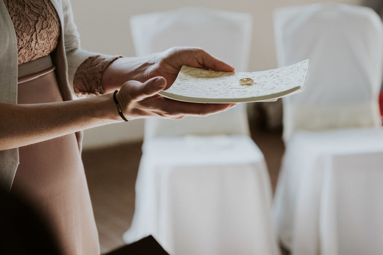 Midsection of woman holding ring on papers at temple