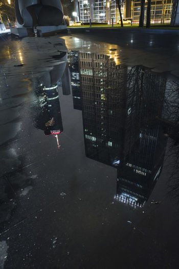 Reflection of illuminated buildings in puddle on street